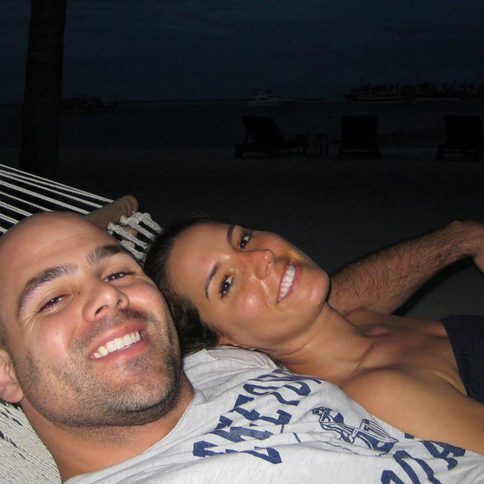 Two people laying on a hammock